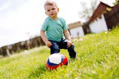 Adorable small boy playing with a soccer ball outdoors stock photography