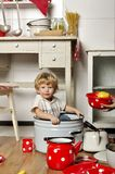 Adorable small child sits in kitchen inside a pan Stock Photo