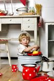 Adorable small child sits in kitchen inside a pan Royalty Free Stock Photos