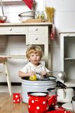 Adorable small child sits in kitchen inside a pan Royalty Free Stock Photography