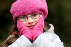 Adorable small girl in bright pink hat. With long dark hair and glasses on beauty autumn background Stock Photography