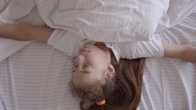 Adorable small girl sleeping in the bed at home. Girl waking up from an alarm clock on her smart watch. Modern. Technology. Carefree childhood stock footage