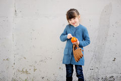 Adorable small girl with tangerine Stock Photo