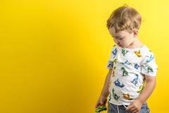 Adorable small three years old boy with cute face expression. On yellow background royalty free stock photos