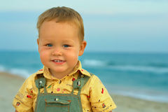 Adorable smiling baby boy standing near the. Close-up portrait of adorable smiling baby boy standing near the seaside Stock Photos