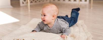 Adorable smiling baby boy in sunny bedroom. Newborn child relaxing. Nursery for young children.Family morning at home Stock Photography