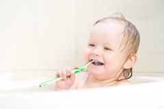 Adorable smiling baby brushing teeth in shower Stock Photography