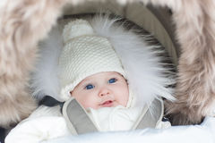 Adorable smiling baby sitting in warm stroller Royalty Free Stock Photos
