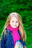 Adorable smiling blond little girl wearing pink scarf Stock Photo