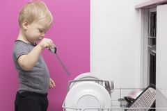 Adorable smiling blonde toddler boy helping in the kitchen taking plates out of dish washing machine stock photography
