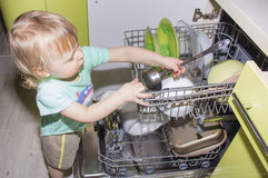 Adorable smiling blonde toddler boy helping in the kitchen taking plates out of dish washing machine Stock Photo