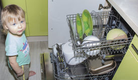 Adorable smiling blonde toddler boy helping in the kitchen taking plates out of dish washing machine Stock Photos