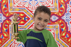Adorable Smiling Boy with Ramadan Lantern. Adorable Smiling Boy with Vintage Lantern over Festive Ramadan Fabric Royalty Free Stock Photos