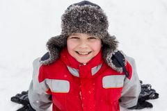 Adorable smiling boy sitting on the snow Royalty Free Stock Photography