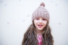 Adorable smiling child girl in beige knitted hat Royalty Free Stock Images