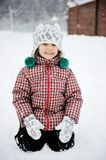 Adorable smiling child girl has fun in the snow Royalty Free Stock Photos