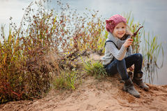 Adorable smiling child girl sitting with stick on river side with sand beach Stock Images