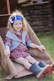 Adorable smiling child girl sitting in wheelbarrow in spring garden Royalty Free Stock Photos
