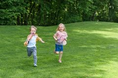 Adorable smiling children with badminton rackets running together. In park stock photography
