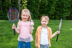 Adorable smiling children holding badminton rackets and shuttlecock. In park royalty free stock photography