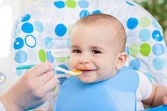 Adorable smiling cute baby eating mash Royalty Free Stock Photography