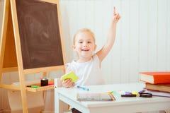 Adorable smiling girl doing homework stock photos