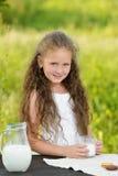 Adorable smiling girl having breakfast drinking milk outdoor summer. Little cute girl drinking a glass of milk in garden. Adorable curly kid having breakfast Royalty Free Stock Photos