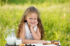 Adorable smiling girl having breakfast drinking milk outdoor summer. Little cute girl drinking a glass of milk in garden. Adorable curly kid having breakfast Stock Photo