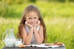 Adorable smiling girl having breakfast drinking milk outdoor summer. Little cute girl drinking a glass of milk in garden. Adorable curly kid having breakfast Royalty Free Stock Photo