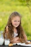 Adorable smiling girl having breakfast drinking milk outdoor summer. Little cute girl drinking a glass of milk in garden. Adorable curly kid having breakfast Royalty Free Stock Image