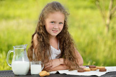 Adorable smiling girl having breakfast drinking milk outdoor summer. Little cute girl drinking a glass of milk in garden. Adorable curly kid having breakfast Stock Photos
