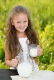 Adorable smiling girl having breakfast drinking milk outdoor summer. Little girl holding glass of milk outdoor. Curly kid having breakfast. Summer time. Healthy Stock Photos