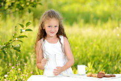 Adorable smiling girl having breakfast drinking milk outdoor summer. Little girl holding glass of milk outdoor. Curly kid having breakfast. Summer time. Healthy Royalty Free Stock Image