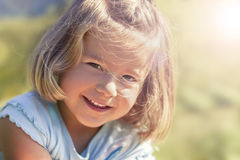 Adorable smiling girl outdoors in nature. Stock Photos