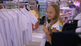 Adorable smiling girl trying and fitting white blouse in boutique. Blonde child choosing clothes for school in store stock footage