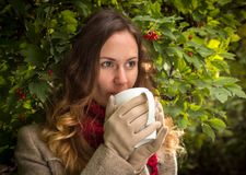 Girl in warm clothes on autumn park tasting a hot beverage royalty free stock image