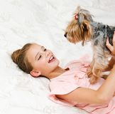 Adorable smiling happy little girl child playing with puppy yorkshire terrier. At home royalty free stock photos