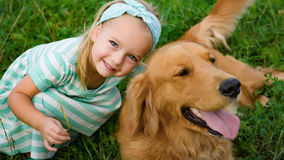 Adorable smiling little blond girl playing with her cute pet dog. Golden retriever royalty free stock photos