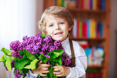 Adorable smiling little boy with blooming purple lilac flowers Royalty Free Stock Images