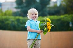 Little boy with bunch of sunflowers outdoors Royalty Free Stock Images