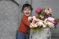 Adorable smiling little boy with flowers by the fireplace Stock Image