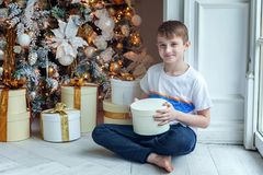 Young boy opens a gift under a Christmas tree Royalty Free Stock Image