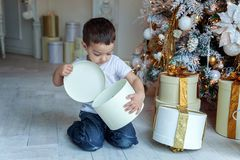 Young boy opens a gift under a Christmas tree Royalty Free Stock Photo