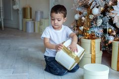 Young boy opens a gift under a Christmas tree Royalty Free Stock Images