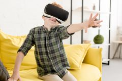 Adorable smiling little boy using virtual reality headset. At home stock photo
