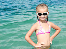 Adorable smiling little girl on beach vacation. In sunglasses Stock Photo