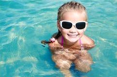 Adorable smiling little girl on beach vacation Stock Photos
