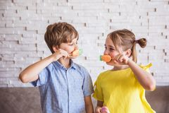 Adorable girl and boy holding colorful sweet meringues on a stick on Easter day royalty free stock photography