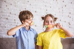 Adorable girl and boy holding colorful sweet meringues on a stick on Easter day stock photos