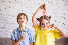 Adorable girl and boy holding colorful sweet meringues on a stick on Easter day royalty free stock image